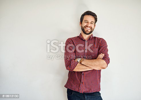 Portrait of a happy and confident young man standing posing against a gray wall
