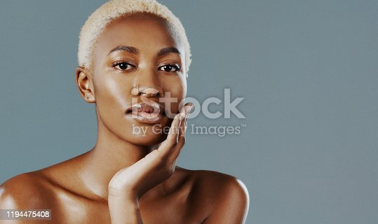 Cropped shot of an attractive young woman standing alone with her hand on her face against a gray studio background