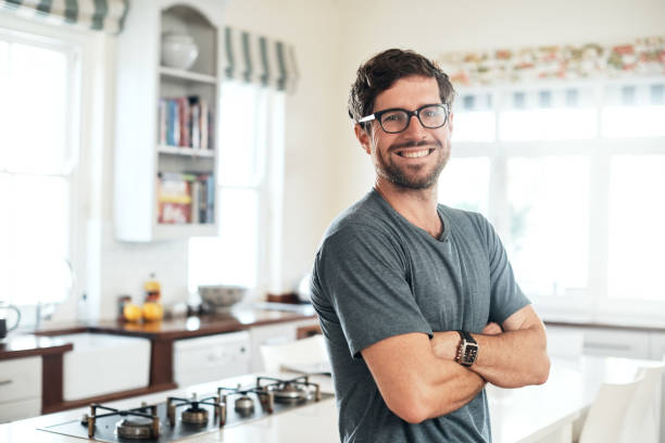 Confidence - practice it daily Portrait of a confident and happy young man at home bachelor stock pictures, royalty-free photos & images