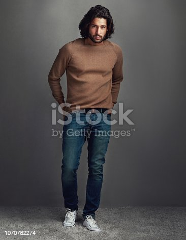 Studio shot of a handsome young man posing against a gray background