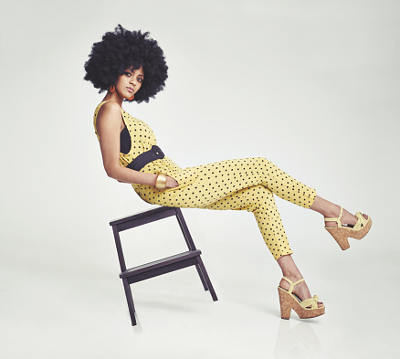 A young woman wearing a 70s retro jumpsuit while balancing on a stool in the studio
