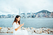 Confidence young Asian woman checking text messages on a smartphone with the iconic Hong Kong skyline in the background
