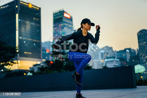 istock Confidence young sports woman exercising and stretching outdoors against urban cityscape during sunset 1134281922