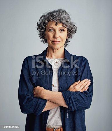 Studio portrait of a confident mature woman posing against a gray background