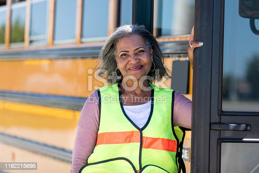 Portrait of beautiful mature African American female school bus driver standing in front of a school bus.