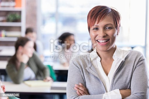 Cheerful mid adult African American school teacher smiles while in front of her classroom. She is looking at the camera.