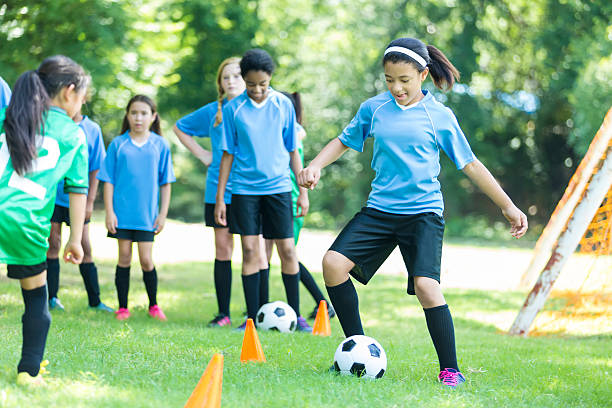 confident african american soccer player practices with team - kinder die schnell arbeiten stock-fotos und bilder