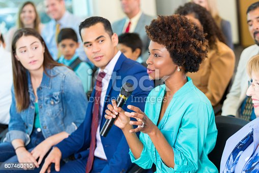 istock Confident African American woman asks question during a meeting 607460110