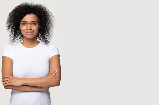 Confident African American woman in glasses standing with copy space
