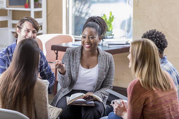 confident african american woman leads bible study - geführtes lesen stock-fotos und bilder