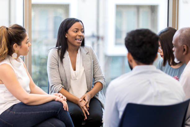 Confident African American woman shares departmental report. When asked, an African American woman shares the report for her department confidently. staff meeting stock pictures, royalty-free photos & images