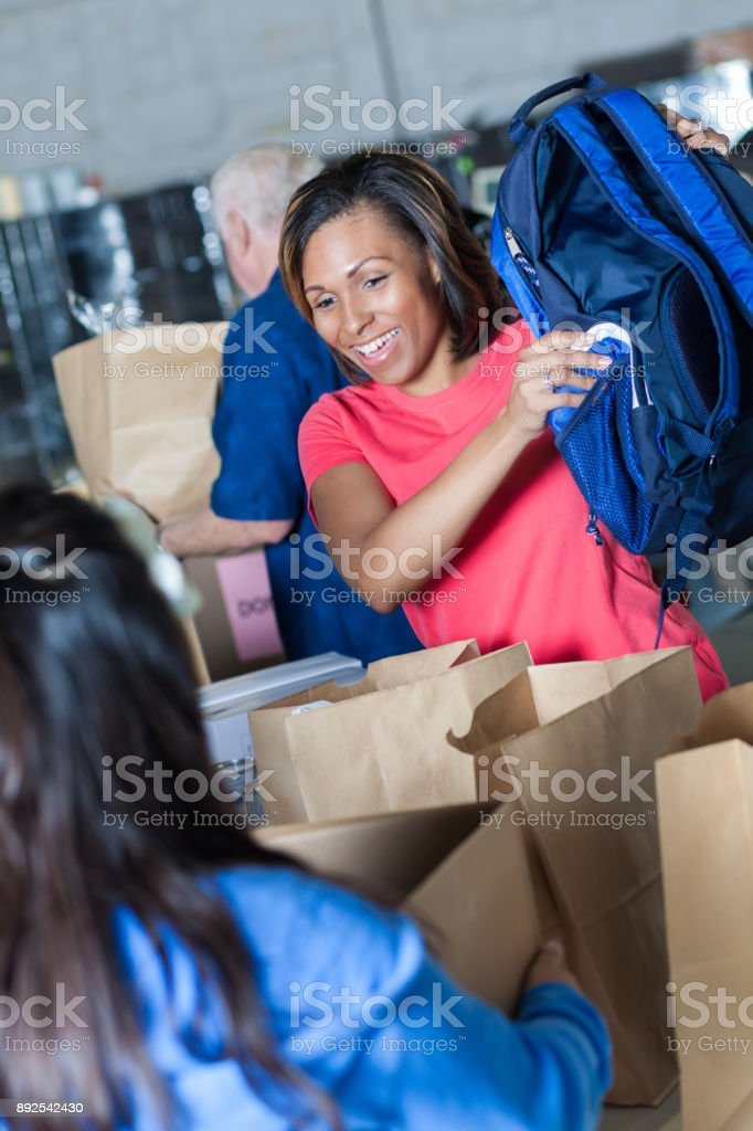 Confident African American woman volunteering during clothing drive stock photo