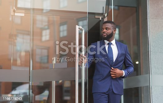Handsome confident african businessman in formal suit walking out of modern office center, copy space