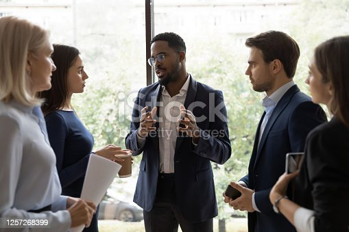 1085713886 istock photo Confident African male leader telling diverse colleagues about new project 1257268399
