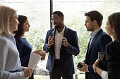 istock Confident African male leader telling diverse colleagues about new project 1257268399