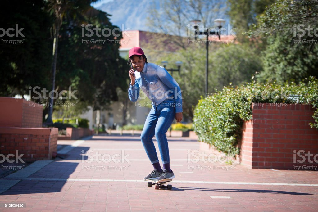 Confident African male on his skateboard while on his mobile phone stock photo