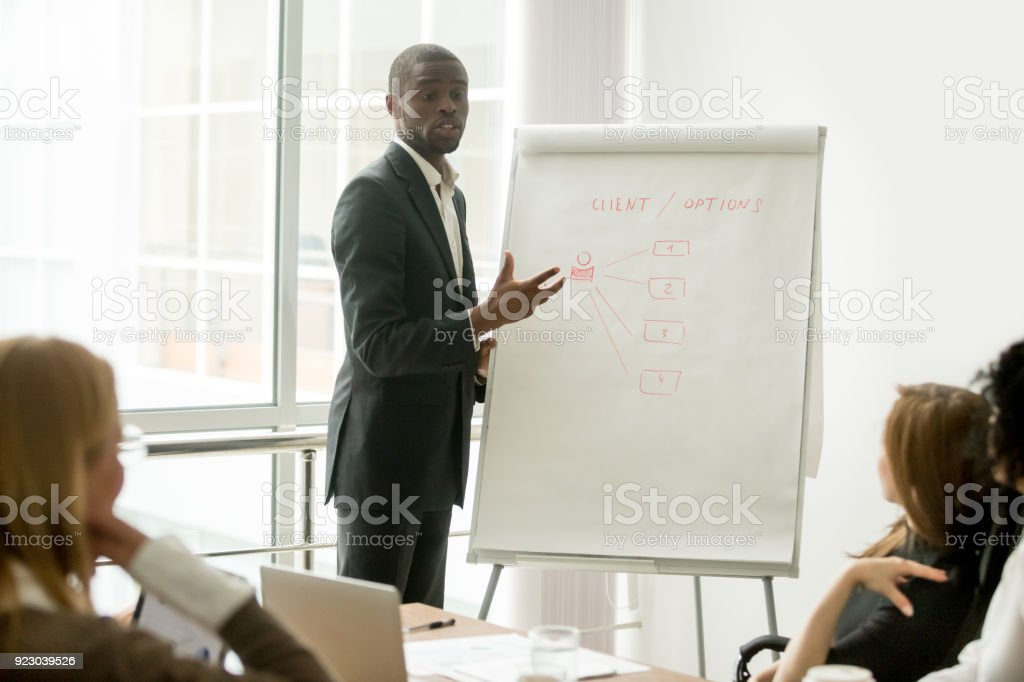 Confident african speaker giving presentation to multi-ethnic group with flipchart stock photo
