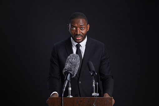 Waist up portrait of confident African-American man standing at podium and giving speech against black background, copy space