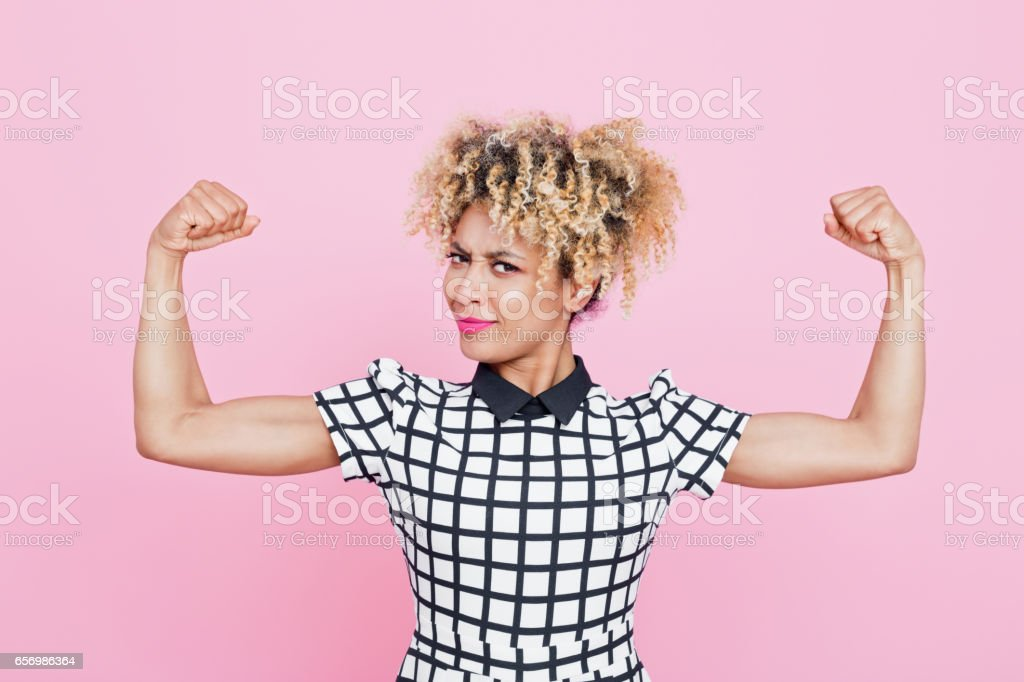 Confident afro american young woman flexing arms Studio portrait of strong afro american young woman flexing her muscles. Pink background. 20-24 Years Stock Photo