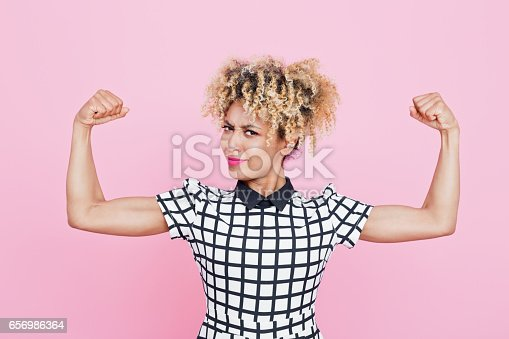 657442382istockphoto Confident afro american young woman flexing arms 656986364