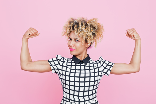 657442382 istock photo Confident afro american young woman flexing arms 656986364