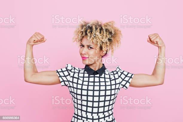 Confident Afro American Young Woman Flexing Arms Stock Photo - Download Image Now