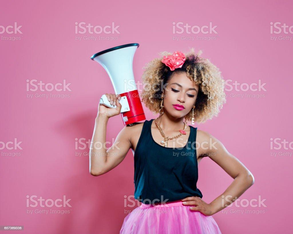 Confident afro woman holding megaphone stock photo