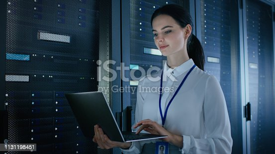 1131198396istockphoto Confident and Beautiful Female IT Engineer is Working on Laptop in Data Center while Standing Before Server Rack. Running Diagnostics or Doing Maintenance Work. 1131198451