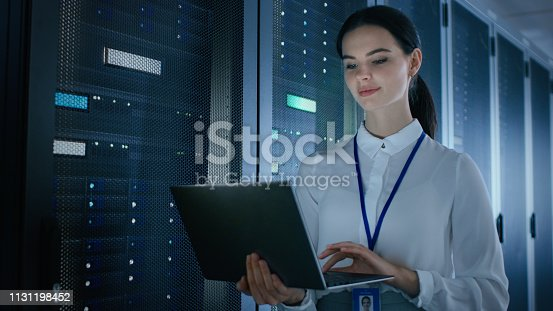 1131198396istockphoto Confident and Beautiful Female IT Engineer is Working on Laptop in Data Center while Standing Before Server Rack. Running Diagnostics or Doing Maintenance Work. 1131198452