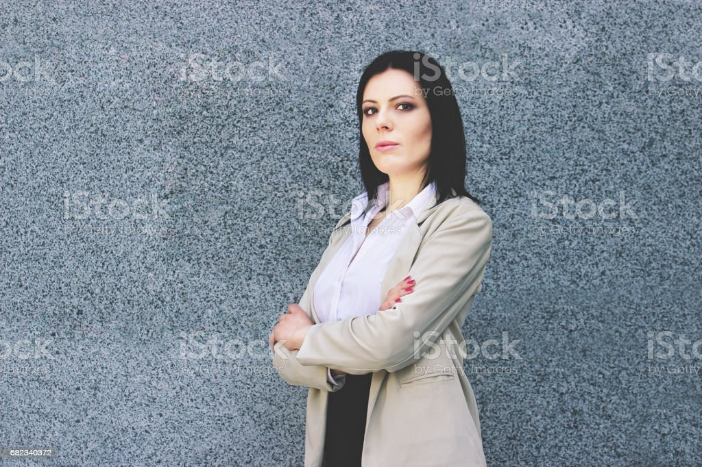 Confident and beautiful. Portrait of attractive and confident business woman in smart casual wear keeping arms crossed while standing against grey background. zbiór zdjęć royalty-free