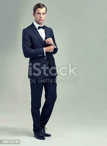 A full length studio shot of a handsome young man in a stylish vintage suit