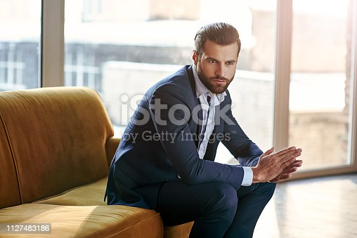 Confident and concentrated. Thoughtful handsome businessman is thinking while sitting in his modern office about business concept while sitting on sofa in his modern office