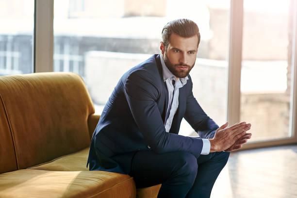selbstbewusst und konzentriert. nachdenkliche schöne geschäftsmann denkt beim sitzen in seinem modernen büro über geschäftskonzept sitzend auf sofa - sexsymbol stock-fotos und bilder