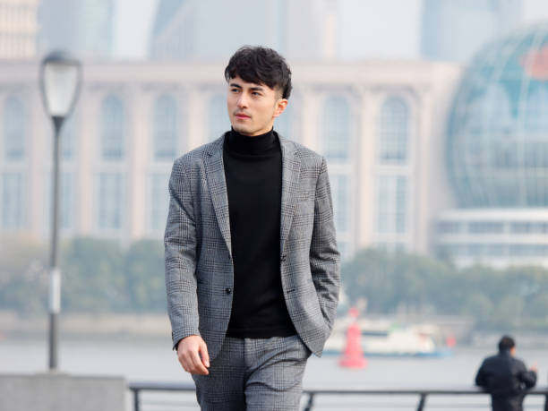 Confident and handsome Chinese young business man in casual suit walking outdoor with hand in his pocket against Shanghai bund background, Chinese businessman lifestyle concept. stock photo