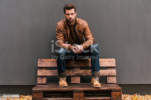 Handsome young man sitting on the wooden pallet and looking at camera with grey wall in the background and orange fallen leaves on the floor