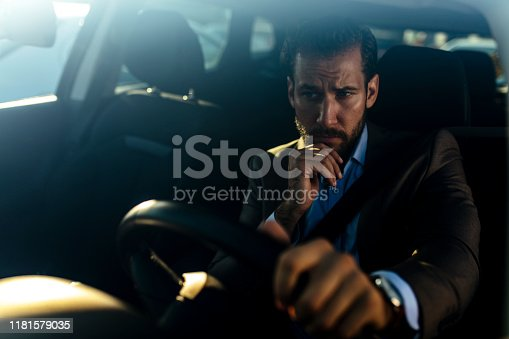 849721378istockphoto Confident and serious businessman inside his car 1181579035
