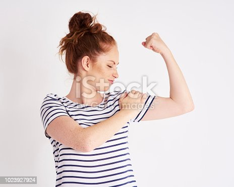 istock Confident and strong woman showing her bicep at studio shot 1023927924