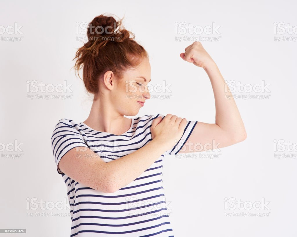 Confident and strong woman showing her bicep at studio shot stock photo