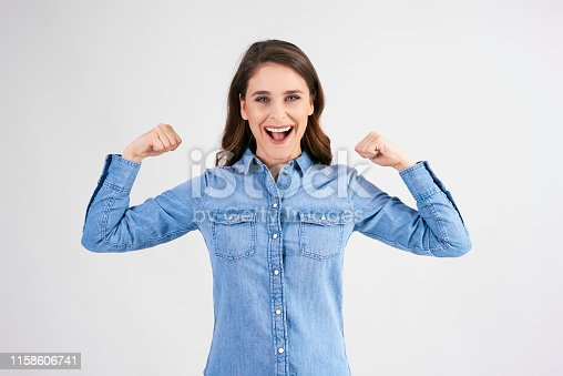 657442382istockphoto Confident and strong woman showing her bicep 1158606741