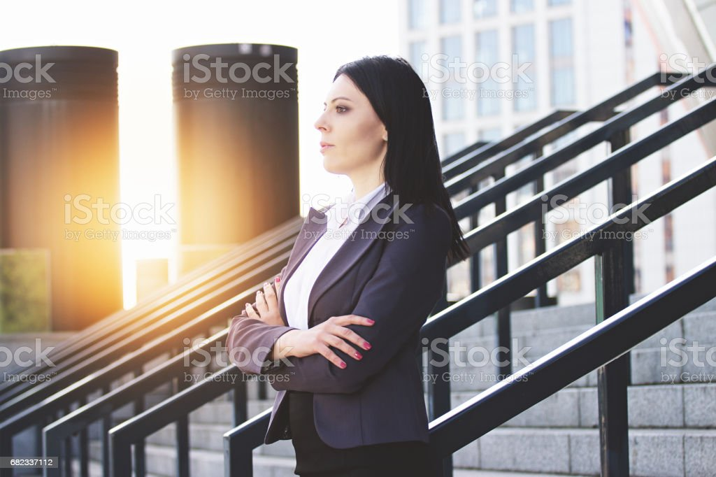 Confident and successful leader. Profile portrait of confident and beautiful business woman in smart casual wear keeping arms crossed while standing against office building. zbiór zdjęć royalty-free