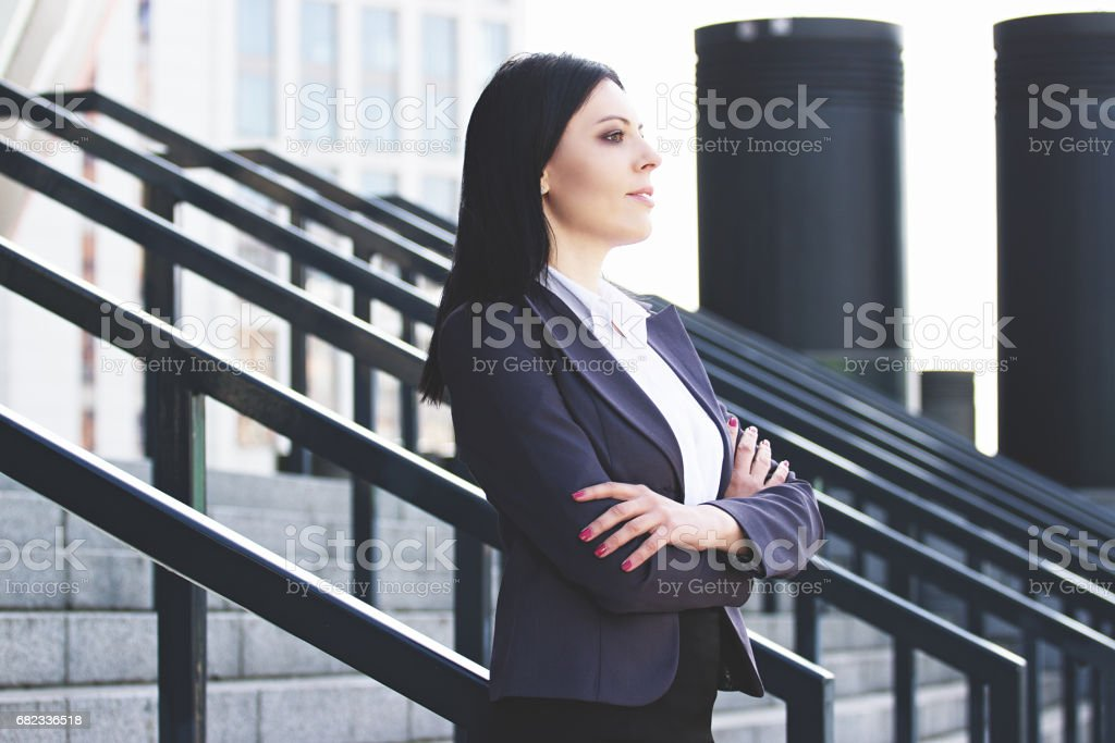 Confident and successful. Portrait of successful business woman in smart casual wear keeping arms crossed while standing near office building. zbiór zdjęć royalty-free