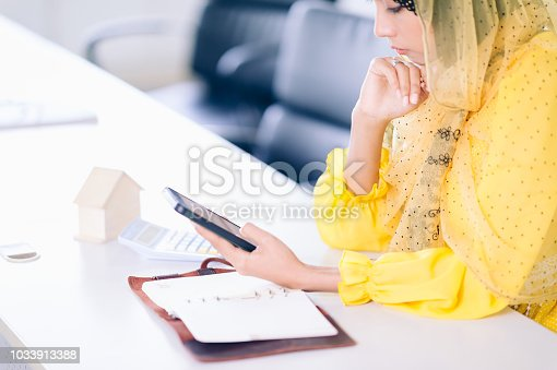 istock Confident Arabian Businesswoman working space.Smile Female arab working  and thinking buy a new house 1033913388