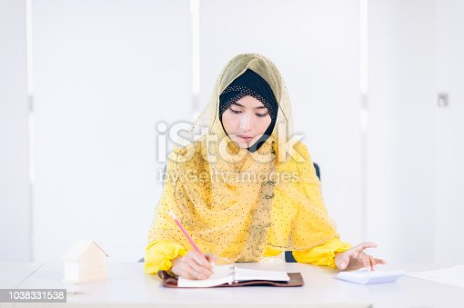 istock Confident Arabian Businesswoman working space.Smile Female arab take note on work place 1038331538