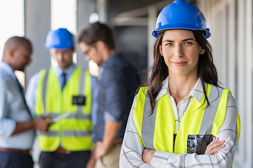 Portrait of woman engineer at building site looking at camera with copy space. Mature construction manager standing in yellow safety vest and blue hardhat with crossed arms. Successful confident architect at construction site with team discussing in background.