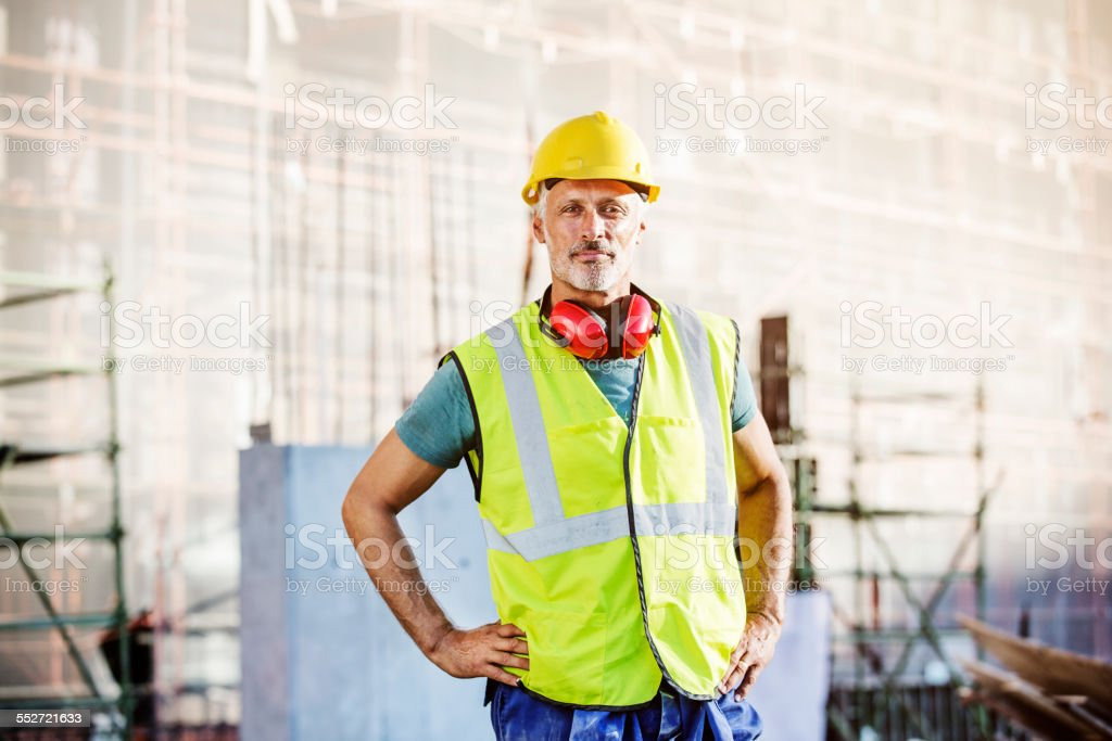 Confident architect standing at construction site stock photo
