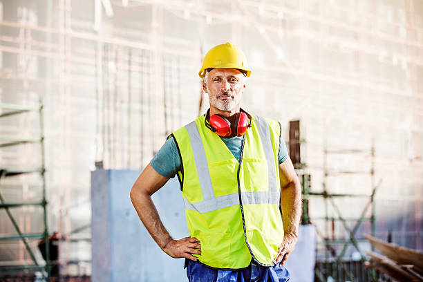 confident architect standing at construction site - builders stock photos and pictures