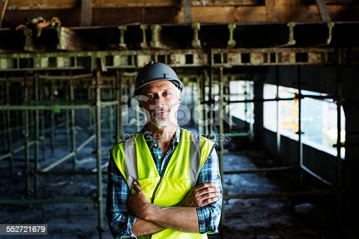 istock Confident architect standing at construction site 552721679
