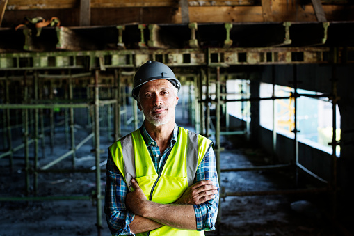 Portrait of confident male architect standing arms crossed at construction site