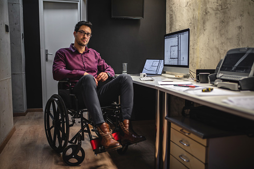 Confident and modern architect in a wheelchair, working in his office.