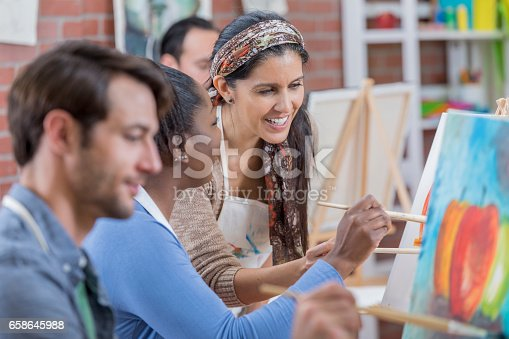 658645980 istock photo Confident art instructor works with students 658645988